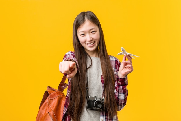 正面を指している飛行機アイコン陽気な笑顔を保持している若いアジア女性。