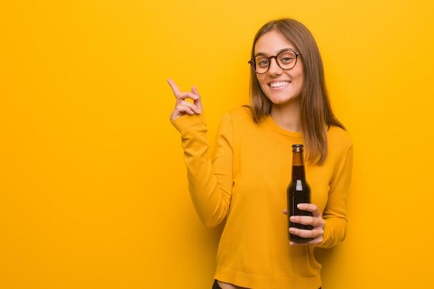 Молодая милая кавказская женщина указывая к стороне с пальцем. она держит пиво.