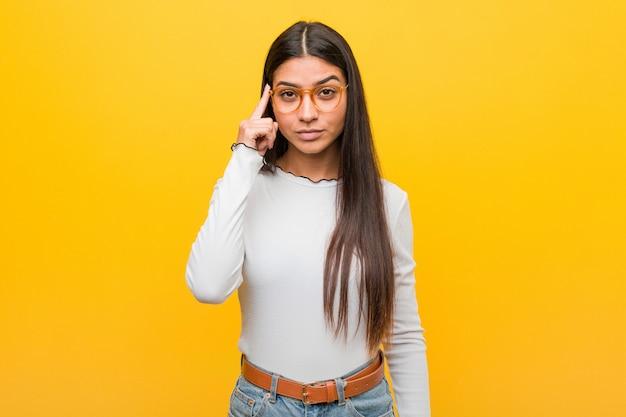 黄色の背景に指で寺院を指して、考えて、タスクに焦点を当てた若いかなりアラブの女性。