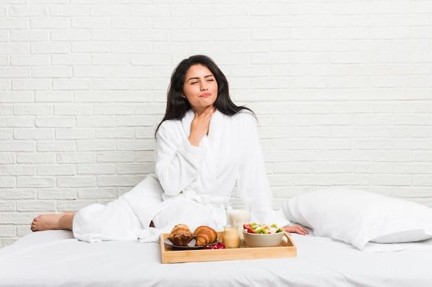 ベッドで朝食をとっている若い曲線の女性は、ウイルスや感染症のために喉の痛みに苦しんでいます。