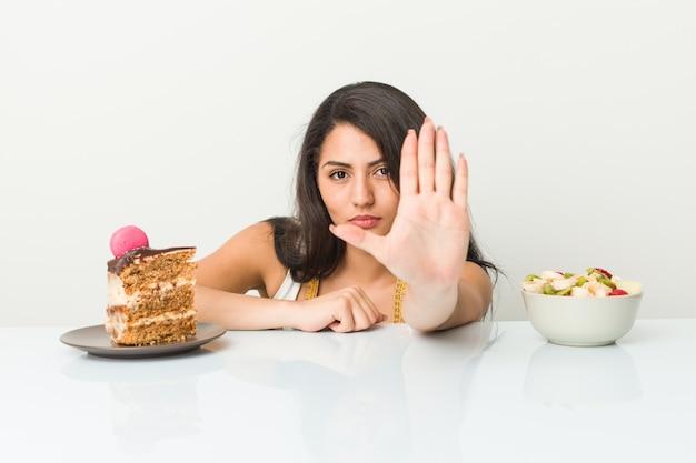 Молодая испанская женщина выбирая между тортом или плодоовощ стоя при протягиванная рука показывая знак стопа, предотвращая вас.