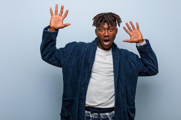 Молодой африканский темнокожий мужчина в пижаме шокирован неизбежной опасностью