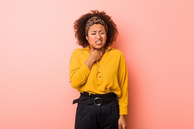 ピンクの壁に座っている若いアフリカ系アメリカ人女性は、ウイルスや感染症により喉の痛みに苦しんでいます。