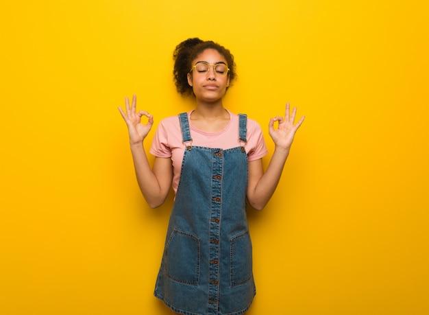 ヨガを実行する青い目を持つ若い黒人アフリカ系アメリカ人の女の子