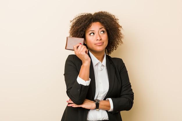 疑いと懐疑的な表情で横向きの財布を保持している若い女性。