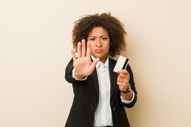 あなたを防ぐ差し出された手を示す伸ばした手で立っているクレジットカードを保持している若い女性。