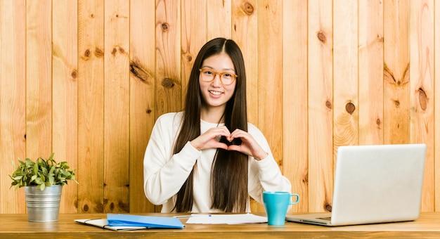 若い女性は笑みを浮かべて、手でハートの形を示す彼女の机で勉強します。