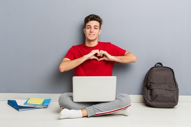 ラップトップを保持している彼の家の床に座っている若い学生男