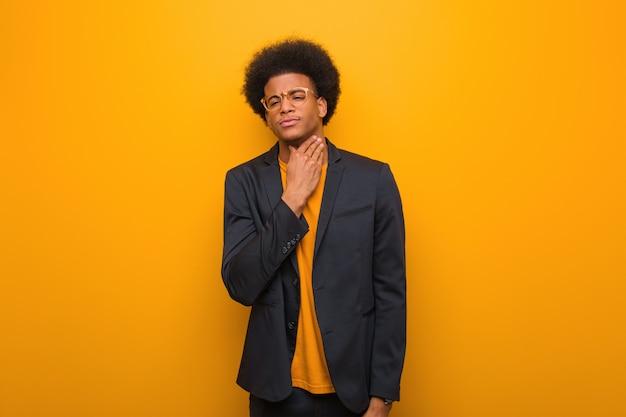 オレンジ色の壁の咳、ウイルスや感染症のため病気の若いビジネスアフリカ系アメリカ人男性