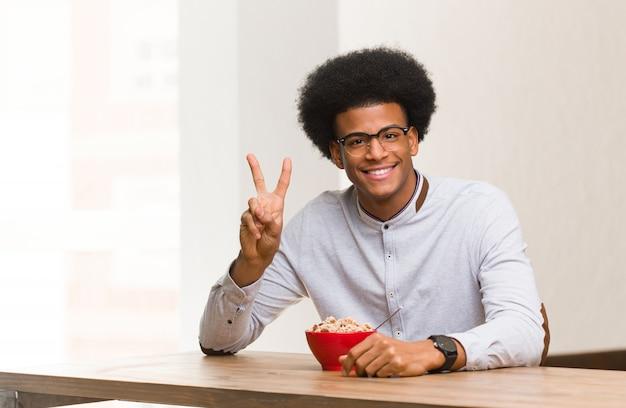 Молодой темнокожий мужчина, весело завтракающий и счастливый делающий жест победы