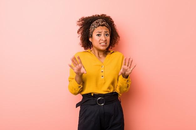 Молодая афро-американская женщина против розовой предпосылки отвергая кто-то показывая жест отвращения.