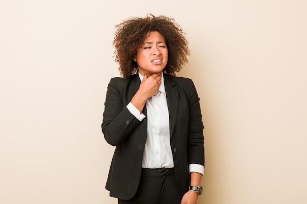 若いビジネスアフリカ系アメリカ人女性は、ウイルスや感染症のため喉の痛みに苦しんでいます。