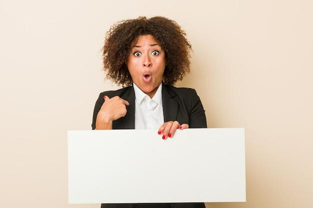 Молодой афроамериканец женщина, держащая плакат удивлен, указывая на себя, широко улыбаясь.