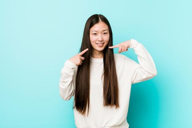 若いかなり中国の女性の笑顔、口に指を指しています。