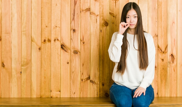 Молодая китайская женщина сидя на деревянном месте с пальцами на губах держа секрет.