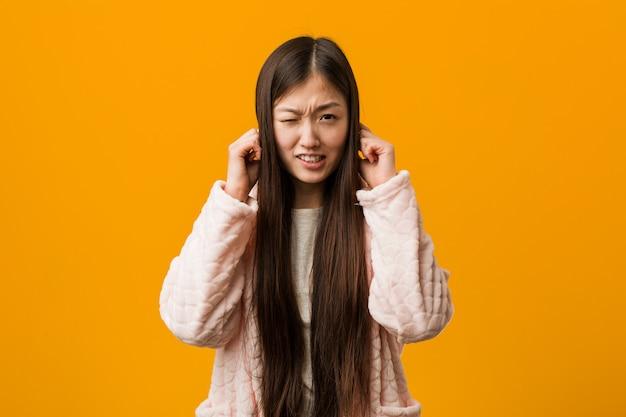 Молодая китайская женщина в пижаме, охватывающих уши своими руками.