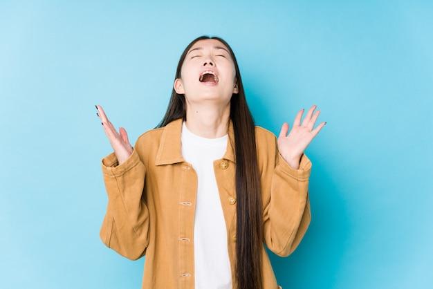 若い中国人女性が青い背景でポーズをとって、空に叫んで、見上げて、欲求不満を分離しました。