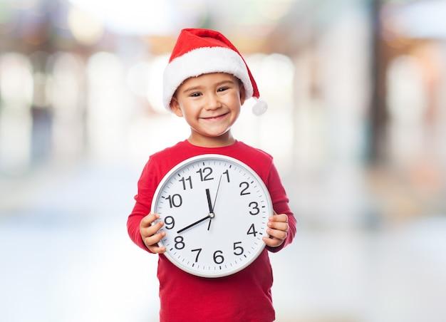 子供は彼の胸の前で時計を保持します