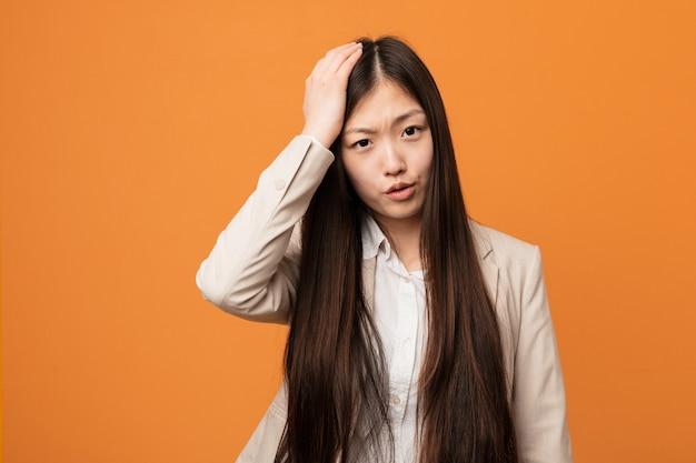 Молодой бизнес китаянка устал и очень сонный держать руку на его голову.