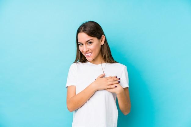 分離された若い白人女性は、胸に手のひらを押して、フレンドリーな表現をしています。コンセプトが大好きです。