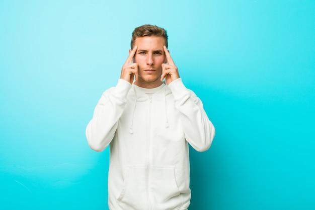 若い白人スポーツ男は、人差し指を頭に向けて、タスクに焦点を当てた。