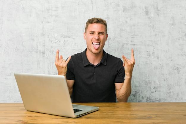 Молодой предприниматель работает со своим ноутбуком на столе, показывая рок жест с пальцами
