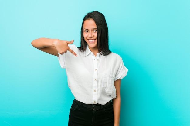 Молодая спокойная женщина против синей стены лица, указывая рукой на рубашку копией пространства, гордый и уверенный