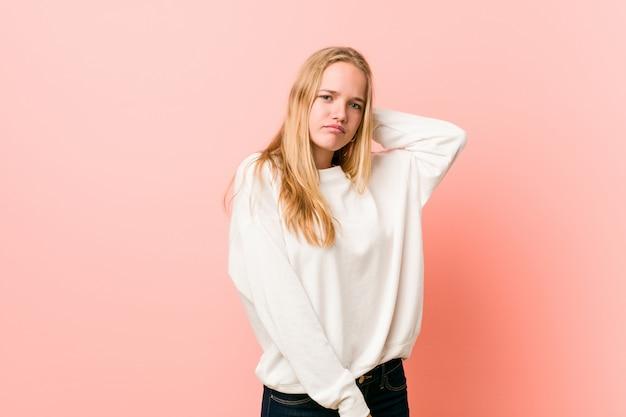 Молодая белокурая женщина подростка страдая боль в шее из-за сидячего образа жизни.