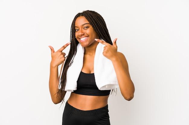 若いスポーツ女性は、口に指を指して、笑顔を分離しました。