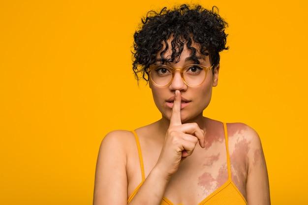 秘密を保持または沈黙を求めて肌のあざを持つ若いアフリカ系アメリカ人女性。
