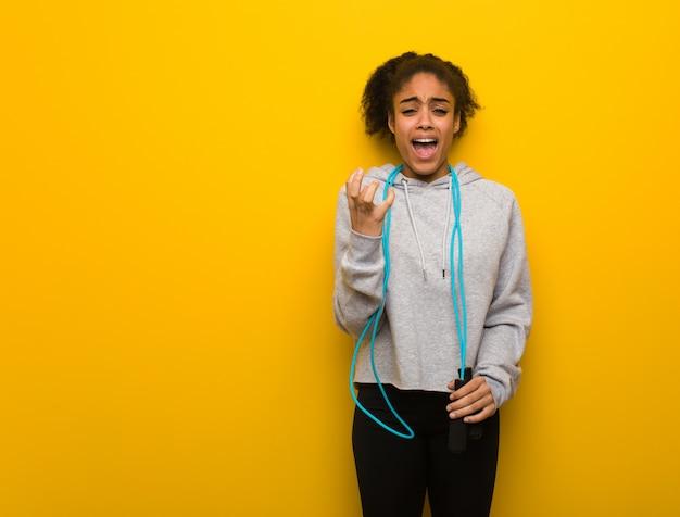 若いフィットネス黒人女性は非常に怖いと恐れています。縄跳びを保持しています。