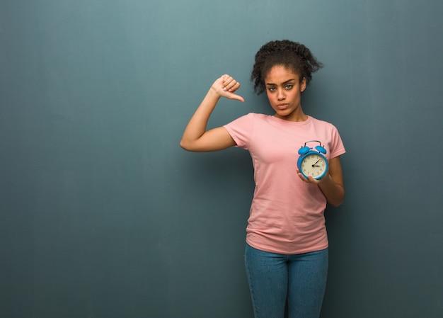 若い黒人女性のポインティング指、次の例。彼女は目覚まし時計を持っています。