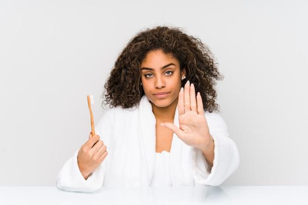 若いアフリカ系アメリカ人の女性が一時停止の標識を示す差し出された手で立っている歯ブラシを持ってあなたを防ぎます。