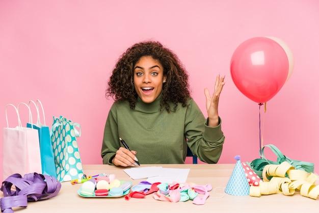 Молодая афро-американская женщина планируя день рождения получая приятный сюрприз, возбужденный и поднимая руки.
