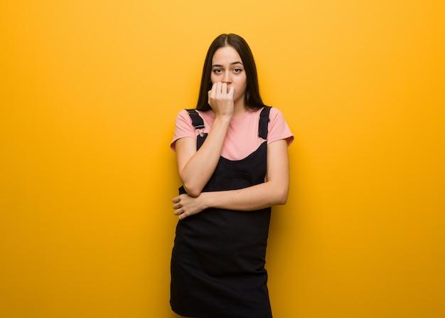 爪をかむ若い自然なきれいな女の子、神経質で非常に心配
