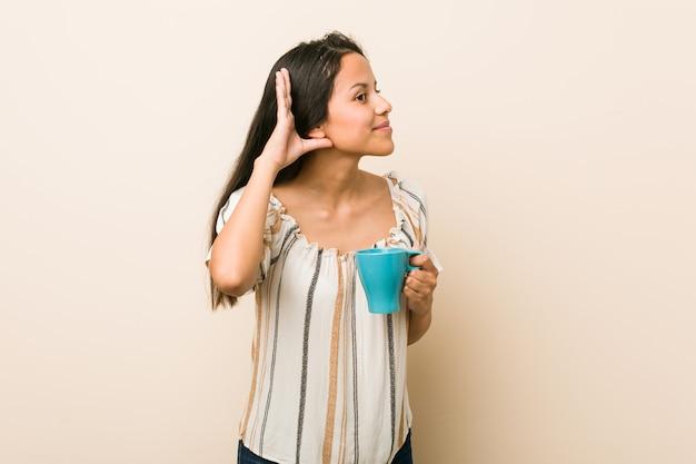 Молодая испанская женщина держа чашку пробуя слушать сплетню.