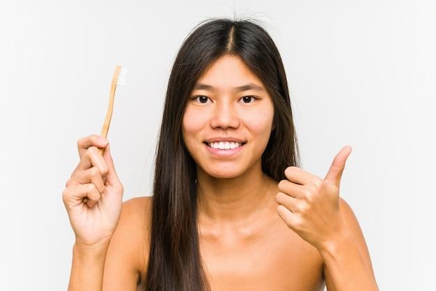 Молодая китайская женщина, держащая зубную щетку, изолирована, улыбаясь и поднимая большой палец вверх