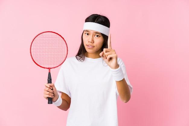 Молодая китайская женщина играя бадминтон в розовой стене имея идею, концепцию воодушевленности.
