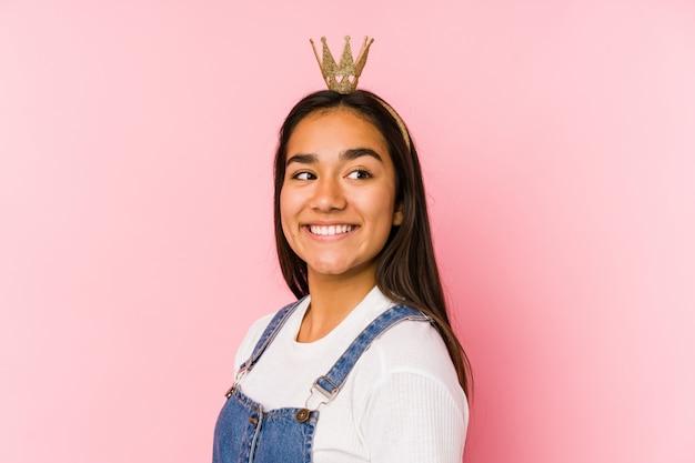 孤立した王冠を身に着けている若いアジアの女性は、笑みを浮かべて、陽気で快適な脇に見えます。