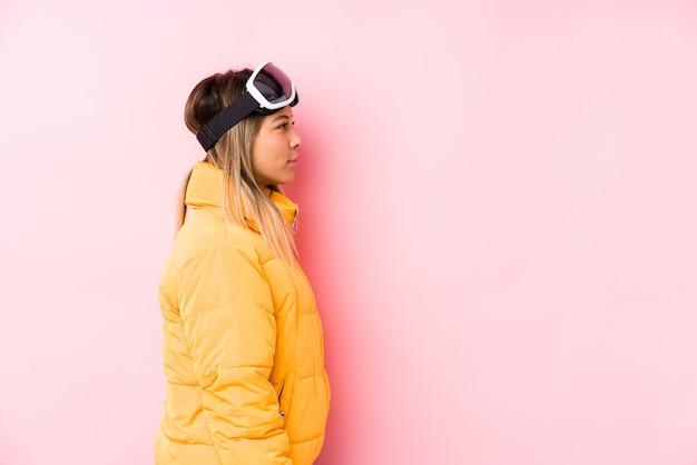 左を見つめるピンクの壁にスキー服を着た若い白人女性、横向きのポーズ。