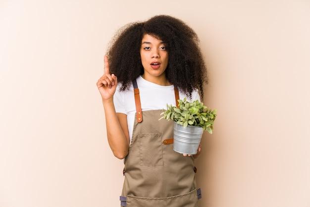 Молодая афро женщина садовника держа изолированный завод иметь некоторую отличную идею, концепцию творческих способностей.
