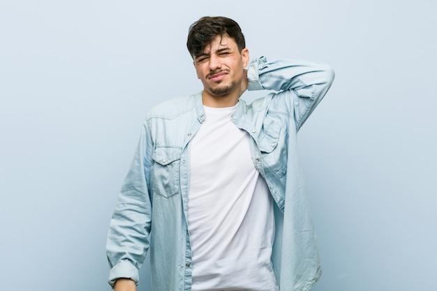 Молодой латиноамериканский спокойный человек, страдающий болью в шее из-за сидячего образа жизни.