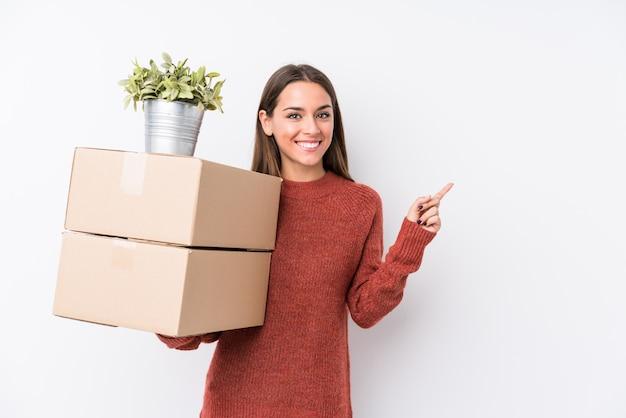 空白を保持しているボックスを保持している若いコーカサス地方の女性は笑みを浮かべて、脇を指して、空白で何かを分離しました。