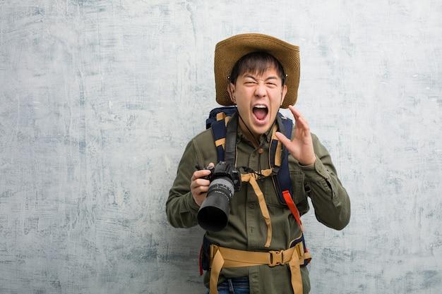 前方に幸せな何かを叫んでカメラを持って若い中国人探検家男