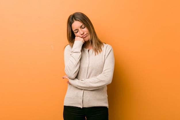 Молодая подлинная харизматическая женщина реальных людей против стены, которая чувствует себя грустной и задумчивой, смотря на пространство копии.