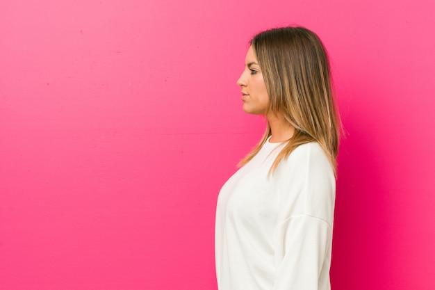 左を見つめる壁に向かって本物の若いカリスマ的な本物の女性、横向きのポーズ。