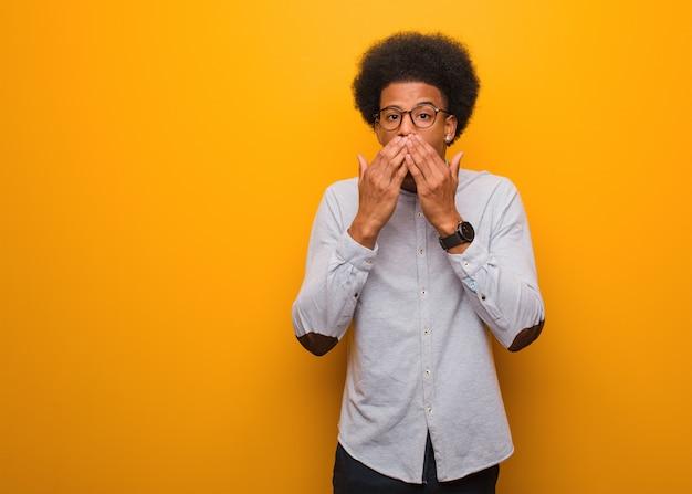 Молодой человек афроамериканца над оранжевой стеной удивлен и шокирован