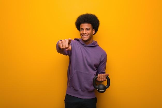 Молодой человек фитнеса афроамериканца держа гантель жизнерадостный и усмехаясь указывающ к фронту