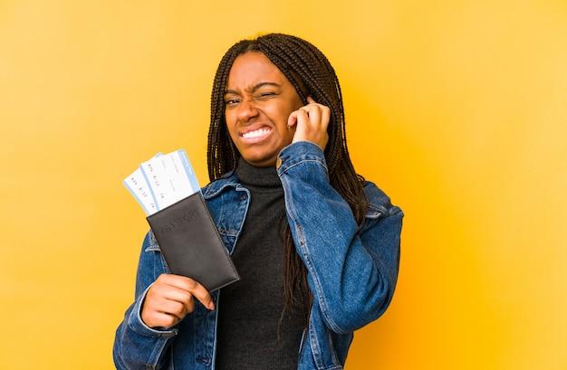 Молодая афро-американская женщина держа пасспорт изолировала покрывать уши руками.