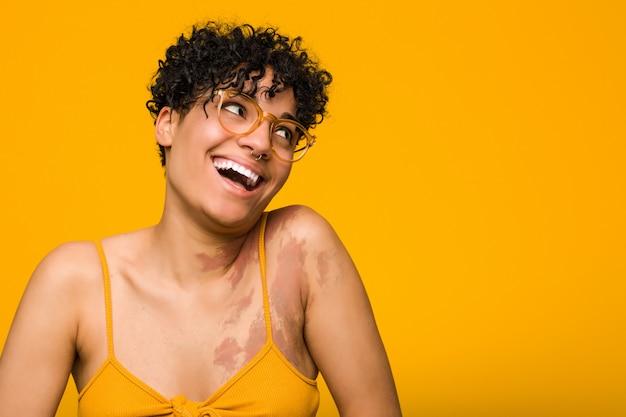 Молодая афроамериканская женщина с отметкой рождения кожи счастливо смеется и весело держит руки на животе.
